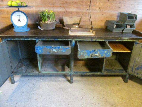 Grote oude ijzeren werkbank met stalen blad