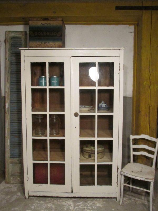Oude brocante keukenkast met glasdeuren