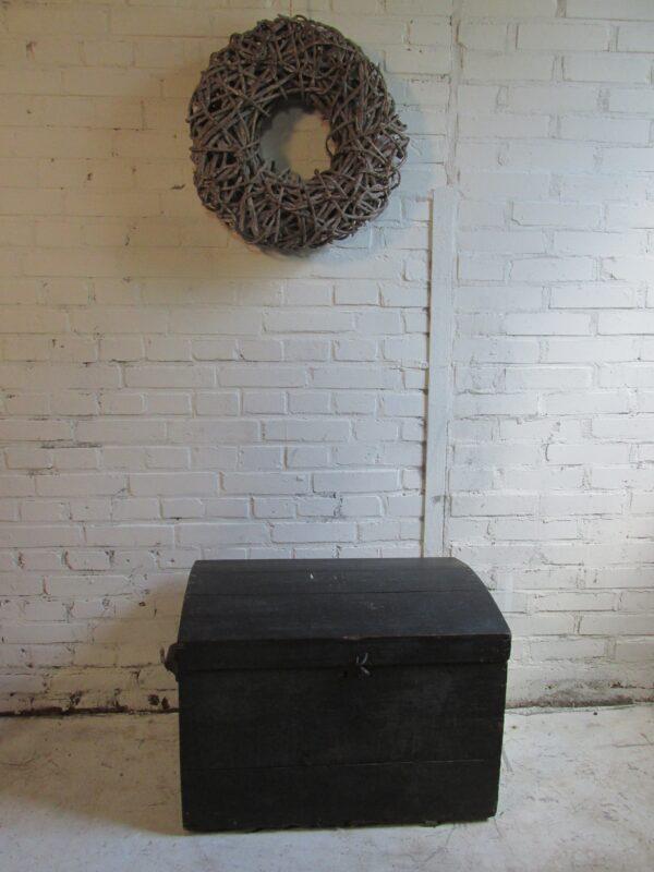 Oude zwarte kist met houten handvatten