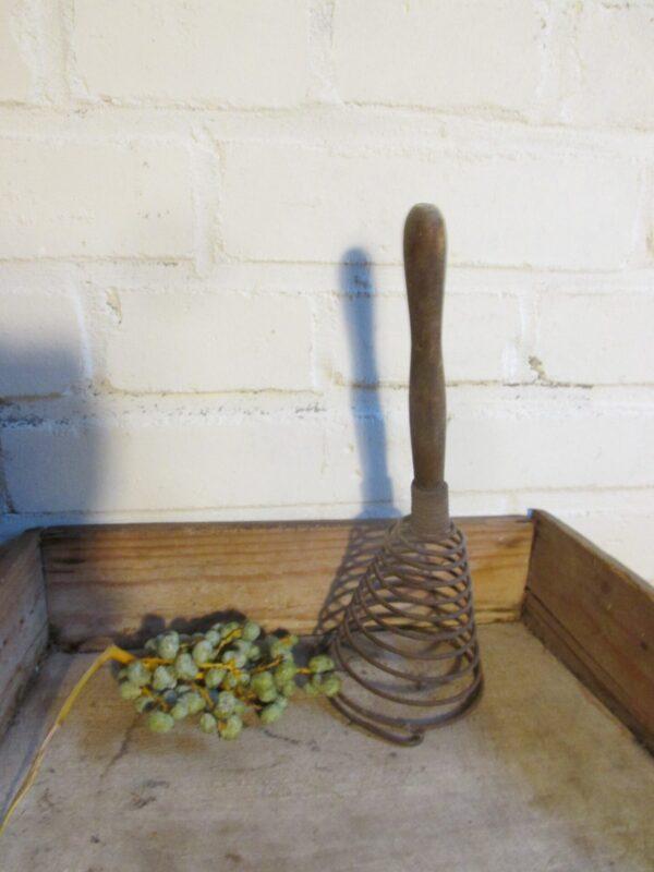 Oude metalen klopper met houten handvat