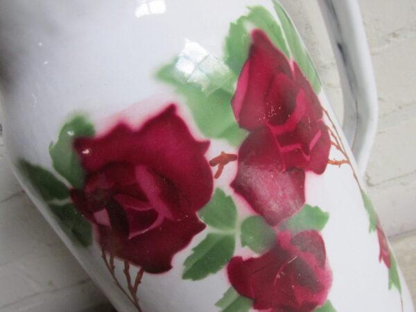 Oude emaille kan met rozen