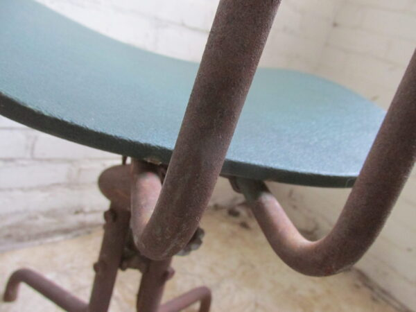 Industriële groene stoel, verstelbaar in hoogte en draaibaar.