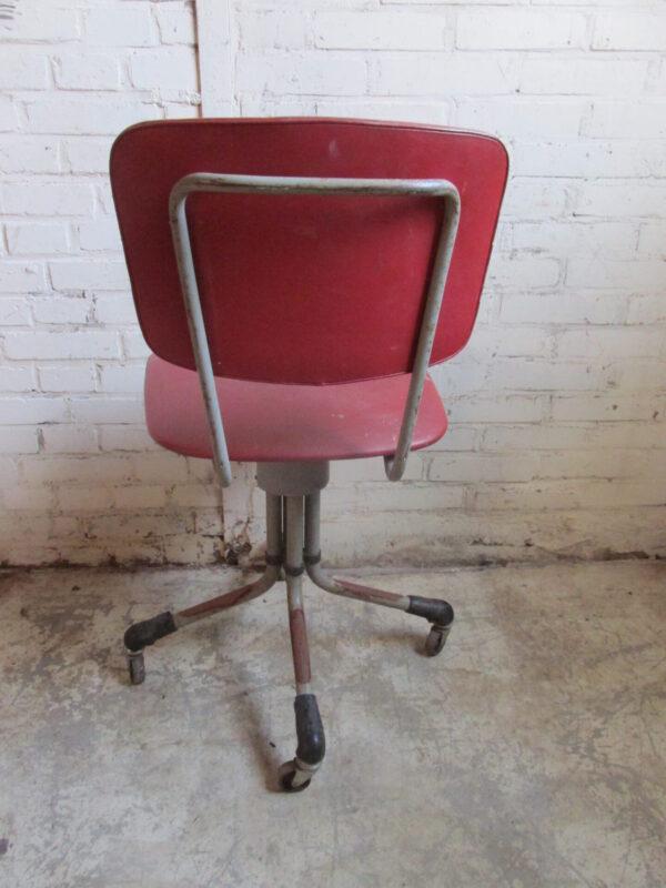 Oude bureaustoel, rood op wielen