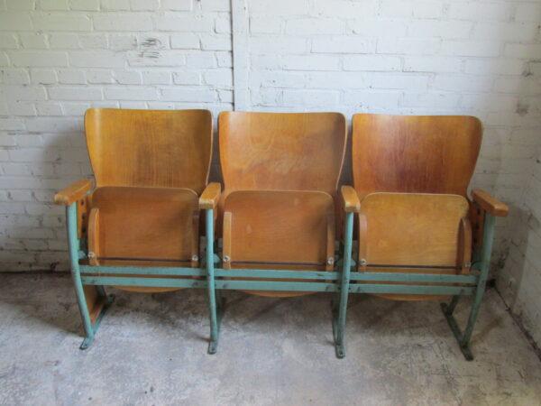 Oude houten bioscoopstoelen met groen stalen frame